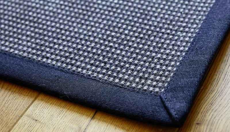 Elfur Natur-Teppich mit kariertem Muster und dunklem Leinenband.