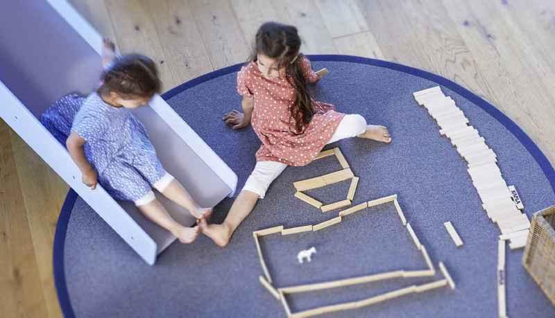 Zwei Kinder spielen auf einem runden Spielteppich.