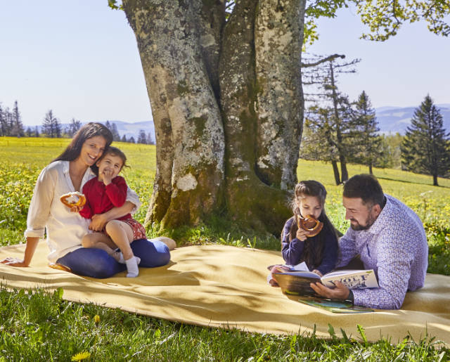 Eine Familie sitzt unter einem Baum auf einem gelben Teppich.
