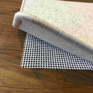Gitternetz Teppichunterlage für glatte und harte Böden, die unter einem Teppich liegt, der gerade an der Ecke hochgehoben wird, sodass die Teppichunterlage sichtbar wird.
